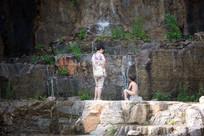 妇女和全裸小男孩看瀑布