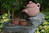 倒水入茶杯的茶壶组合雕塑