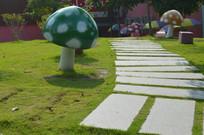 绿色草地蘑菇雕塑石板路