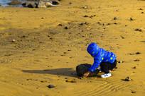海滩上搬礁石的小男孩