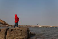 站在海边礁石上的红衣人背影