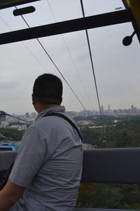 男游客在缆车里远眺广州城