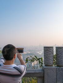 老人在山顶拍摄惠州城市风光