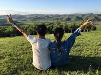 山顶上坐着的情侣背影