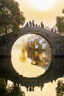 西塘古石桥游客日出倒影