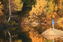 秋林河畔抱着小狗的女人