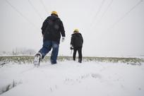 雪中巡线的电力工人背影