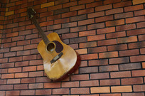红砖墙上的一把吉他