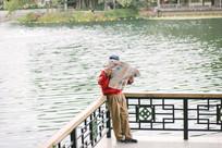 湖边看报的老人