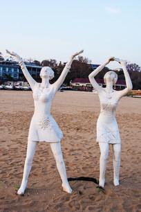 雕塑扬臂仰望天空的两个女人