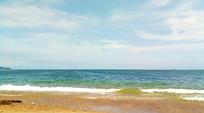 晴空下蔚蓝的海滩泛起浪花