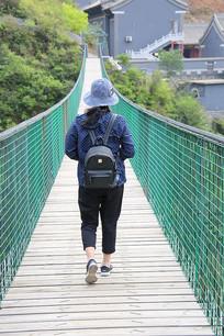 拉索木桥上游客背影
