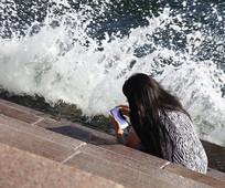 在海边看手机的女孩