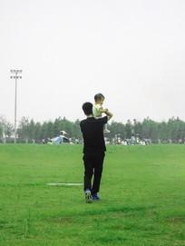 父亲肩膀上的孩子背影摄影图