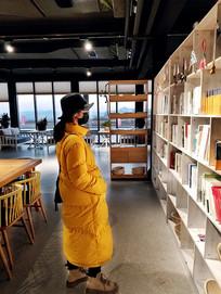书架前站立的黄衣女生
