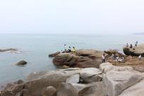 在海边奇特礁石上的人们