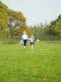 草坪上牵着小手的母女俩