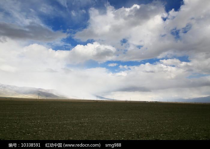 蓝天白云飘过的草场土地图片