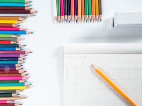 画本旁边排列规则的彩色铅笔