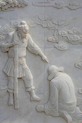 站着的张果老与跪着的官员壁雕