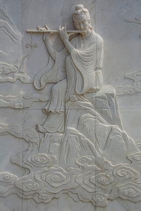 仙人韩湘子坐在祥云山崖上吹箫壁雕