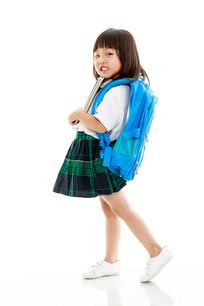 白背景前抱书背书包的小女孩