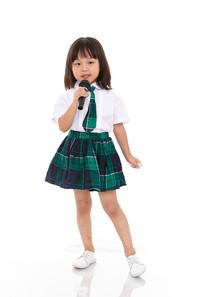 白色背景前拿话筒唱歌的小女孩