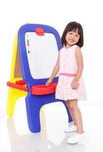 微笑的小女孩站在画架前