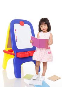 小女孩站在画板边看着书