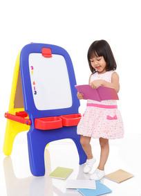 小女孩站在画板边拿着本子读书