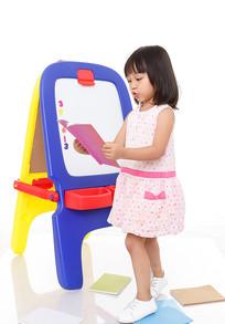 小女孩站在画板前看书