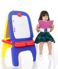 小女孩坐在白色凳子上认真阅读