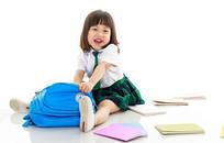 坐在地上散落书本的小女孩