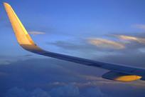 在晚霞中飞行的飞机机翼