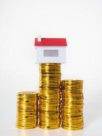 堆叠起来的金币上方红房子