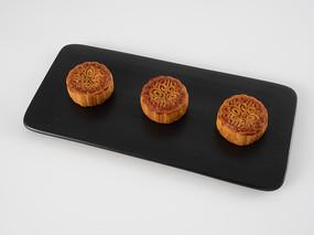 黑色瓷盘上依次排列的三个月饼