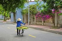 越南推自行车卖水果的妇女