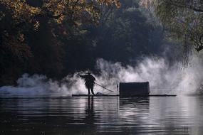 晨雾映衬下打渔人剪影