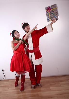 穿圣诞装拿着礼盒的男人和红色礼服的女人