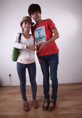 靠在一起手比成心形的青年情侣