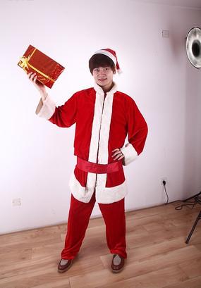 一手拿着礼盒一手叉腰的圣诞装男孩