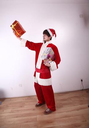 圣诞装男人凝视着右手的红色礼盒
