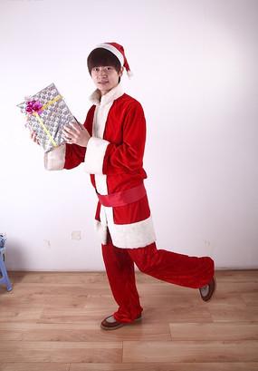 双手轻举礼盒左脚尖着地的圣诞装男人