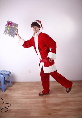 穿着圣诞装拿着礼物摆造型的男模特