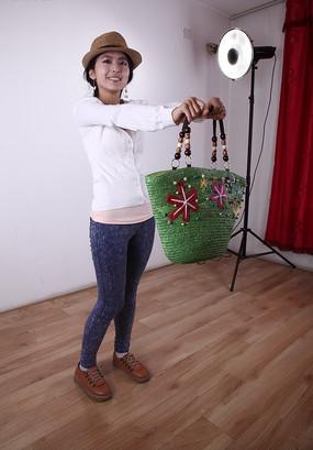 双手提着绿色包包微笑举向前方的美女