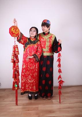 手拿爆竹与红辣椒装饰的古装新郎新娘