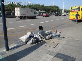 坐在马路上的拾荒老人