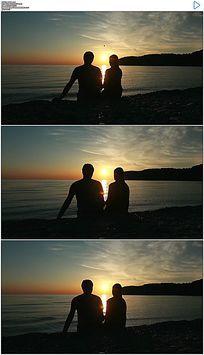 情侣坐在海滩上看夕阳扔石头实拍视频素材