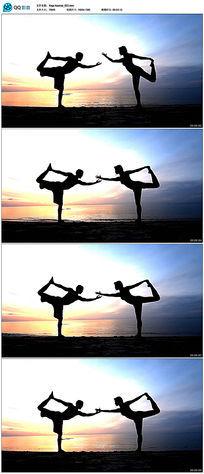 夕阳下海边练瑜伽的情侣