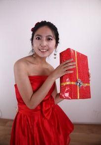 双手举着礼盒微笑的女人